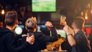 JCLM Solicitors Men watching sport in bar with beer.